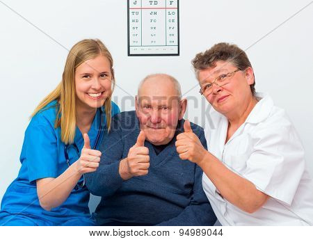 Thumbs Up From Elderly Man And His Caregivers