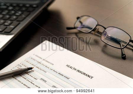 Filling Health insurance form on a wooden table