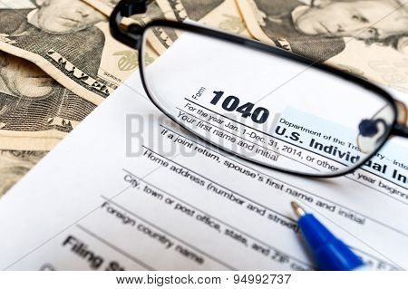 1040 individual tax return form, glasses and dollar bills
