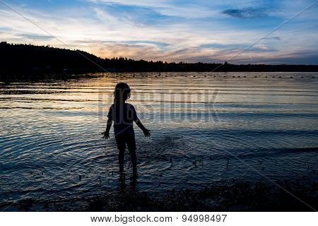 Silhouette Of Little Girl Playing In The Water In Twilight