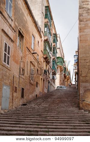 Ancient Staircase Street In Valletta, Malta. Narrow Street With Old Fashioned Balcony, Carved Stone