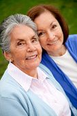 stock photo of elderly woman  - Portrait of an elder mother and daughter smiling outdoors - JPG