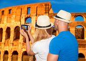 Постер, плакат: Back side of young happy couple taking picture of beautiful gorgeous ancient Coliseum honeymoon vac