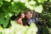 stock photo of pry  - Peeping through the foliage of the men and women who had gathered near a tree kissing  - JPG