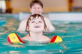 image of floaties  - Happy little kid boy and his father swimming in an indoor swimming pool - JPG