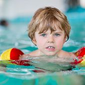 picture of floaties  - Kid boy of 4 years with swimmies learning to swim in an indoor pool. Active and fit leisure for children. ** Note: Soft Focus at 100%, best at smaller sizes - JPG