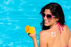 stock photo of sunbathers  - Happy woman with sunscreen lotion funny smiley on her back enjoying summer vacation at swimming pool - JPG