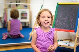 image of creativity  - Little child is drawing with pieces of color chalk on the chalk board - JPG
