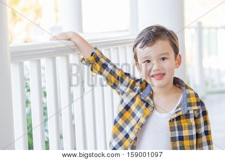 Young Mixed Race Chinese and Caucasian Boy on His Front Porch.
