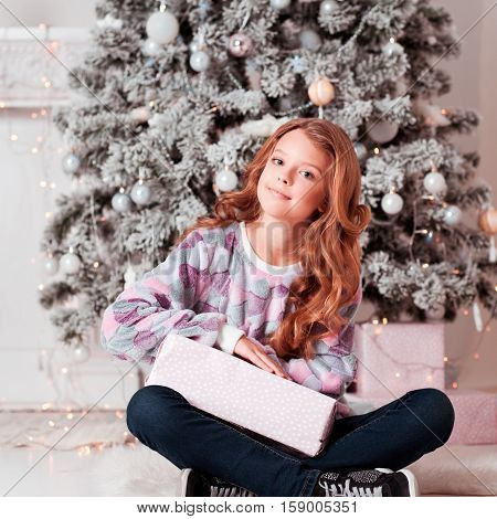 Happy teenager girl 12-14 year old holding Christmas present in room. Sitting on floor. Wearing casual clothes. Looking at camera.