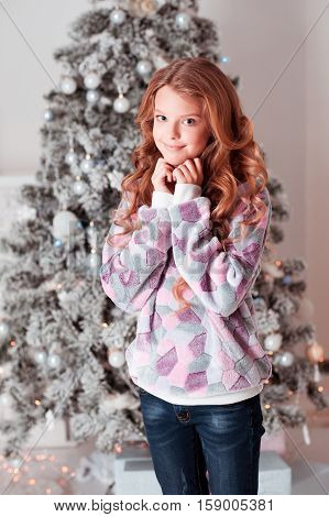 Smiling teen girl 14-15 year old standing over Christmas tree in room. Looking at camera. Cheerful. Celebration.