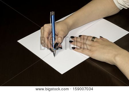 Women`s hands writing on white paper. Clear blank