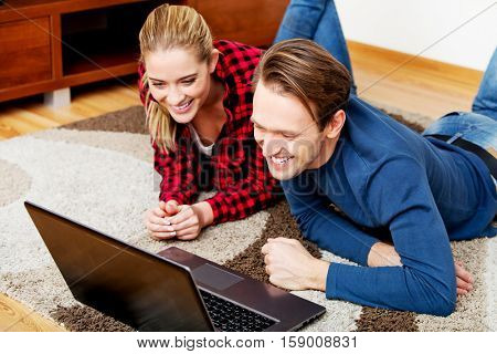 Happy couple lying on the floor with laptop