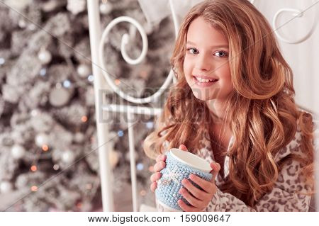 Smiling kid girl 10-12 year old holding tea cup sitting in bed over Christmas tree in room. Looking at camera. Celebration. Holiday time.