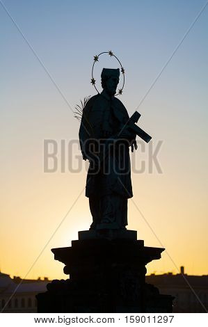 Prague, Czech Republic. Statuette in Charles Bridge at sunrise. St. silhouette against the background of the dawn sky.