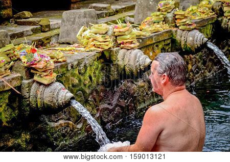Bali Indonesia - August 11: a man washed his body at the Bali Holy Spring Water Temple. on August 11 2011 at Bali Holy Spring Water Temple Indonesia.