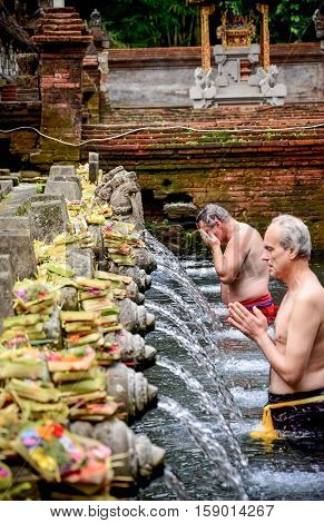 Bali Indonesia - August 11: The old man was washed his body at the Bali Holy Spring Water Temple. on August 112011 at Bali Holy Spring Water Temple Indonesia.