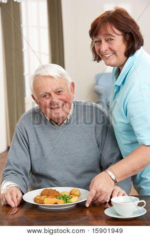 Senior Man Hardlocks Mahlzeit von Betreuern