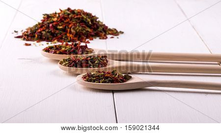 three wooden spoons with dried peppers and seeds (chili peppers habanero jalapeno rawit birds eye chili thai chili) on a white wooden place.