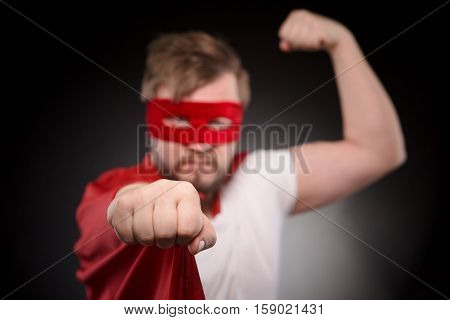 Image of super hero man showing wrist while posing for photographer in studio. Handsome man in red mask ready to save world and help people.