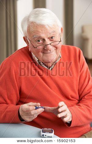 Senior Man Checking Blood Sugar Level At Home