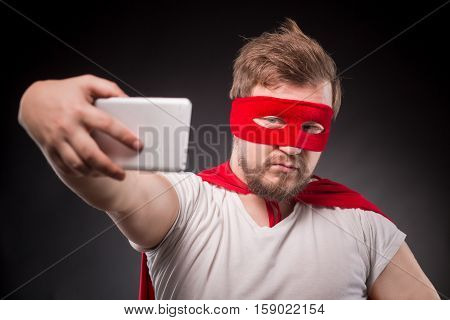 Egoist. Self. Hero. Super Hero. Picture of handsome super hero man with red mask on making super hero for his friends.