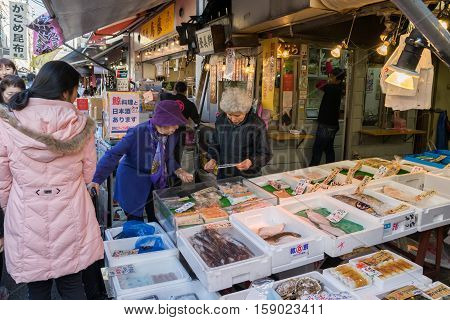 TOKYO, JAPAN - 18 NOV 2016 - Customer shopping fresh seafood in Tsukiji Fish Market, Tokyo, Japan on November 18, 2016.