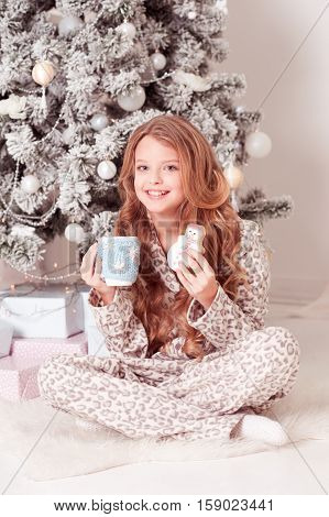 Happy teen girl 10-12 year old having breakfast under Christmas tree in room. Looking at camera. Celebration. Christmas eve.