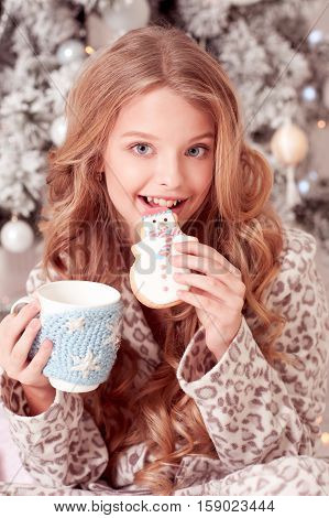 Laughing teen girl 12-15 year old biting cookie drinking tea in room. Christmas tree. Celebration.
