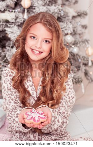 Cheerful teen girl 12-15 year old holding gingerbread in room. Christmas tree. Happy New year.