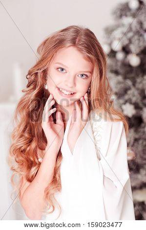 Smiling teen girl 10-15 year old posing over Christmas tree in room. Wearing white elegant dress.