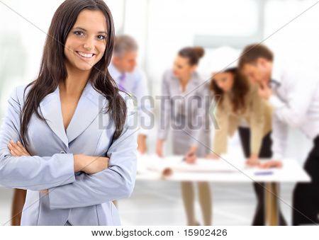 Porträt einer charismatischen Frau bei einem Treffen während ihr Team im Hintergrund arbeiten