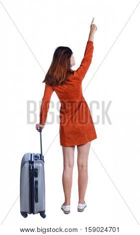 Back view pointing woman with suitcase looking up. Standing young girl. Rear view people collection. Isolated over white background. Girl in red dress standing with gray suitcase and shows up finger