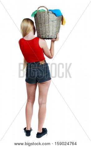 Back view of woman with  basket of dirty laundry. girl is engaged in washing. Rear view people collection.  Isolated over white background. Long-haired blonde in shorts, carrying a basket of laundry.