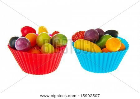 colorful cups full with fruit candy isolated over white background