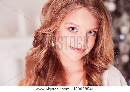 Smiling teen girl 10-15 year old with blonde curly hair in room. Looking at camera. Teegerhood. Celebration.