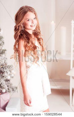 Cheerful teen girl 14-15 year old wearing white dress in room. Looking at camera. Teenagerhood.