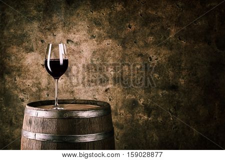 Glass of red wine on wine barrel shot with dark background