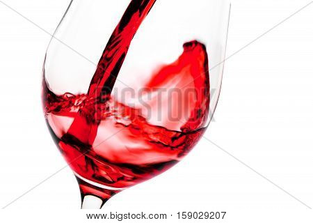 Red wine pouring in glass goblet isolated on white background