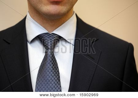 Closeup portrait of businessman in white collar shirt and suit with tie.