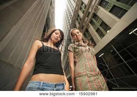 Two beautiful young women in New York City street. Wide angle.