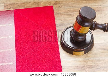 Wooden Law Gavel and legal book close up on wooden desktop, top view
