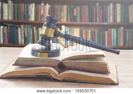 Wooden Law Gavel on open books with a row of law books in library