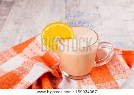 raf coffee closeup with an orange on a wooden table and a napkin