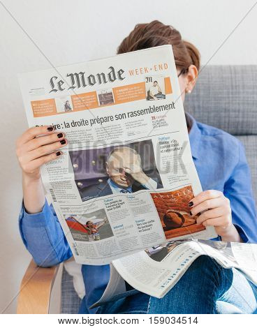 PARIS FRANCE - NOV 29 2016: Woman reading in armcharir Le Monde newspaper with headline and articles about Vladimir Putin - the current President of Russian Federation