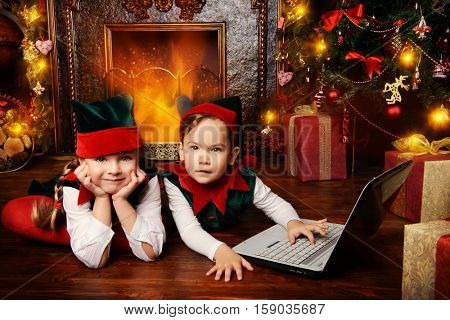 Two cute children in christmas elf costumes in a room beautifully decorated for Christmas. Time of miracles.