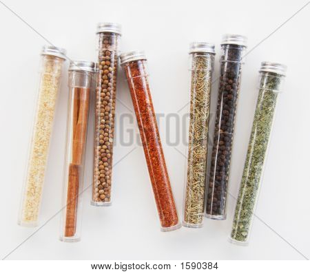 Seven colorful spice containers in a