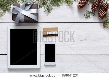 Christmas online shopping background. Cell phone and tablet screen with copy space top view on white wood, credit card and present. Mobile applications and internet commerce on winter holidays concept