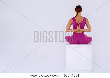 Sport yoga woman practicing yoga sitting and folded hands behind his back. Concept meditation and concentration with copy space Back view