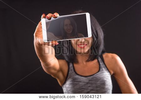 Sports or athletic lady holding mobile or smart phone in front of her and smiling for camera while posing isolated on black background in studio.